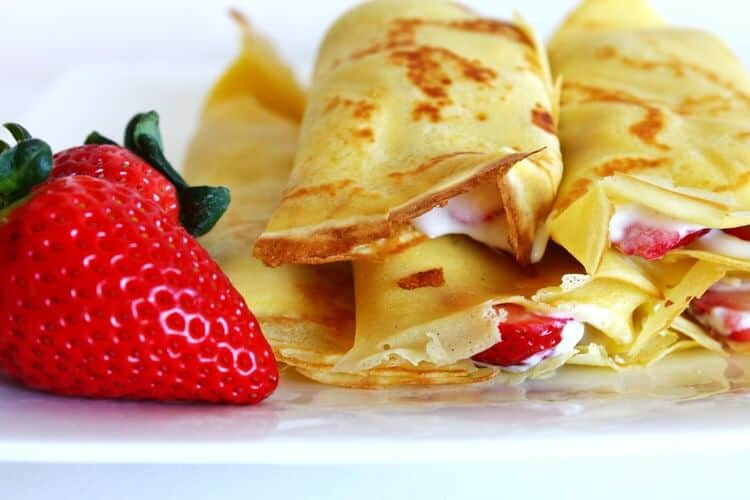 french crepes with whipped cream and strawberries