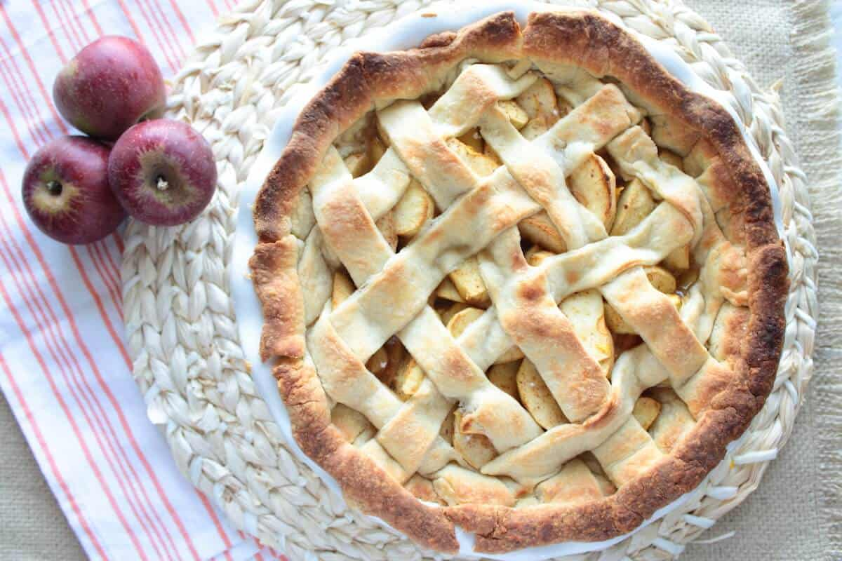 easy apple pie recipe in a pie dish next to apples