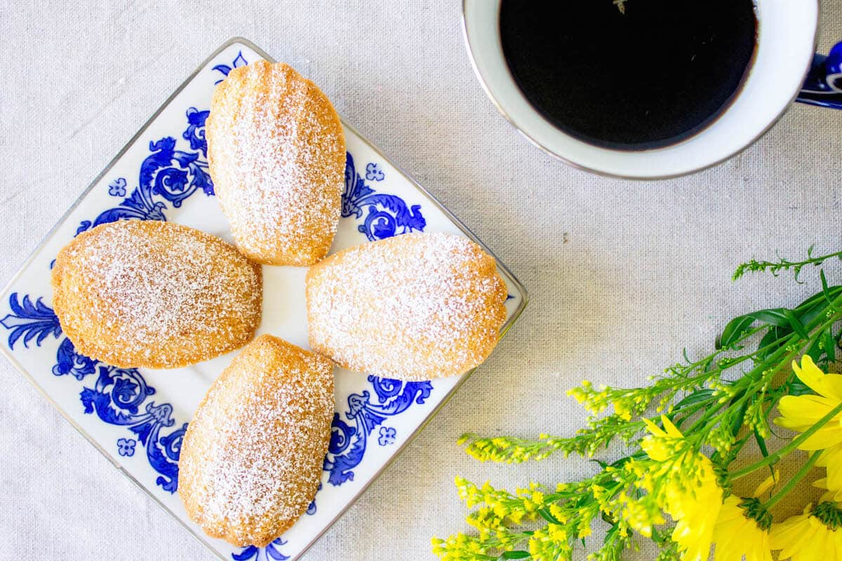 Madeleine cookies on a plate with coffee