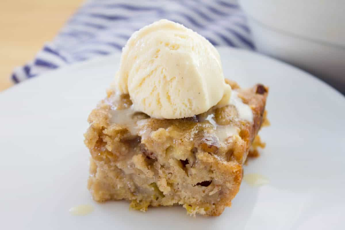 apple spice cake slice with scoop of vanilla ice cream on top