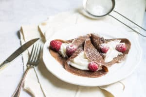 Chocolate Crepes filled with cream and fresh raspberries, then dusted with powdered sugar. So easy and so delicious! Recipe via MonPetitFour.com