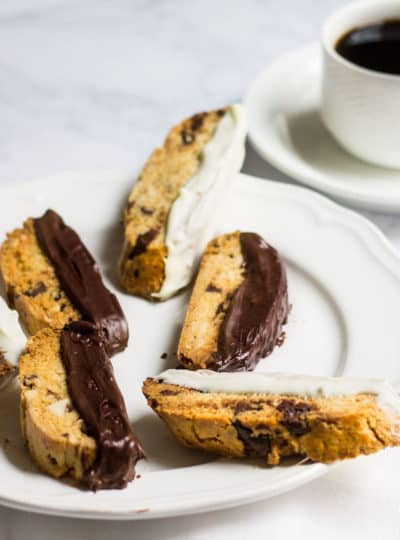 Chocolate-Dipped Almond Biscotti: a crisp almond cookie filled with dark chocolate, orange zest, and almonds. Perfect as a winter dessert, served with a cup of hot coffee. Recipe via MonPetitFour.com