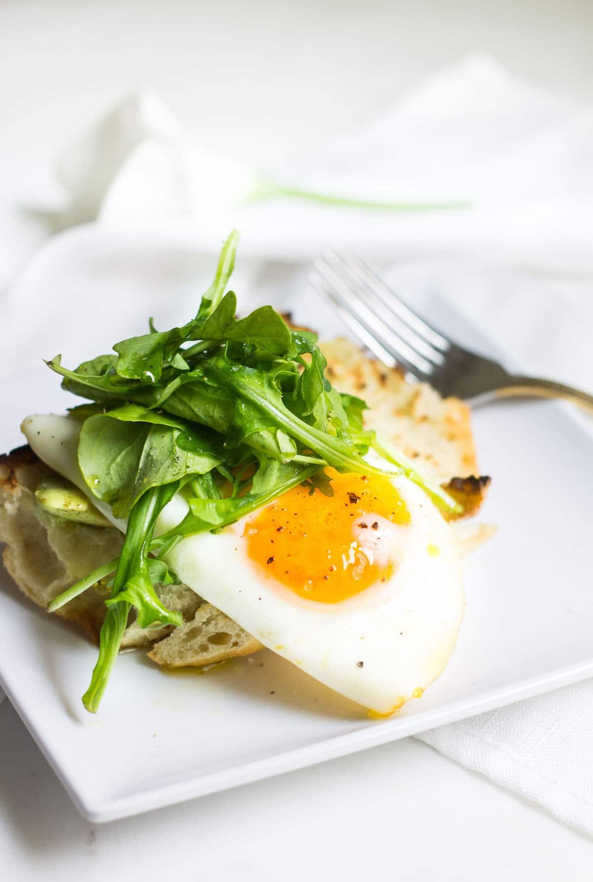 Egg Toast with avocado, arugula, lemon, and olive oil. A perfect breast or lunch! Recipe via MonPetitFour.com