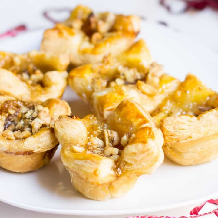 Fig Brie Bites perfect for entertaining! Creamy brie inside golden puff pastry, topped with sweet fig preserves and crunchy walnut pieces. Recipe via MonPetitFour.com