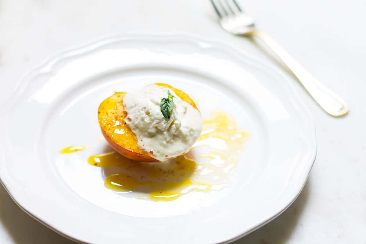 Baked Peaches with Cream: a quick and easy summer dessert made with ripe peaches and freshly whipped cream. A French recipe known as pêches rôties. Recipe via MonPetitFour.com