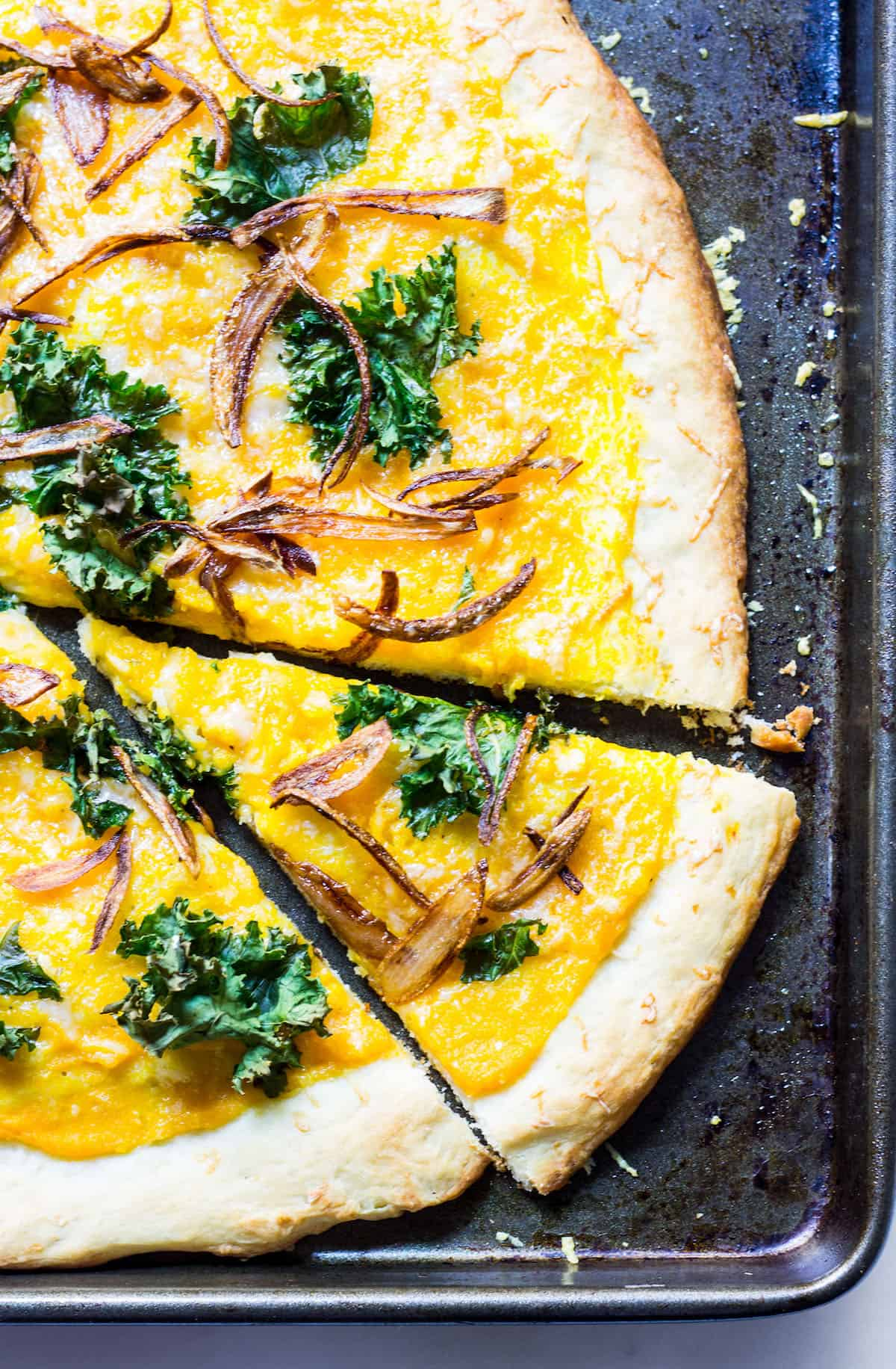 Butternut Squash Pizza: a fall pizza made with butternut squash sauce, gruyere cheese, crispy kale, and crispy shallots all on a homemade pizza crust. Recipe via MonPetitFour.com