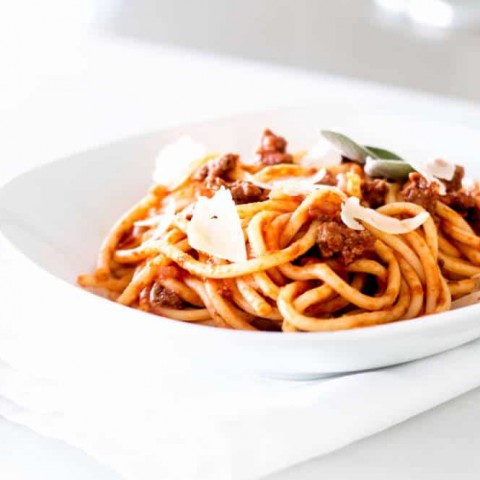 Simple Bolognese Recipe bowl of spaghetti with fresh parmesan shavings and herbs