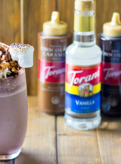 s'mores milkshake in a cup next to Torani syrups and sauces