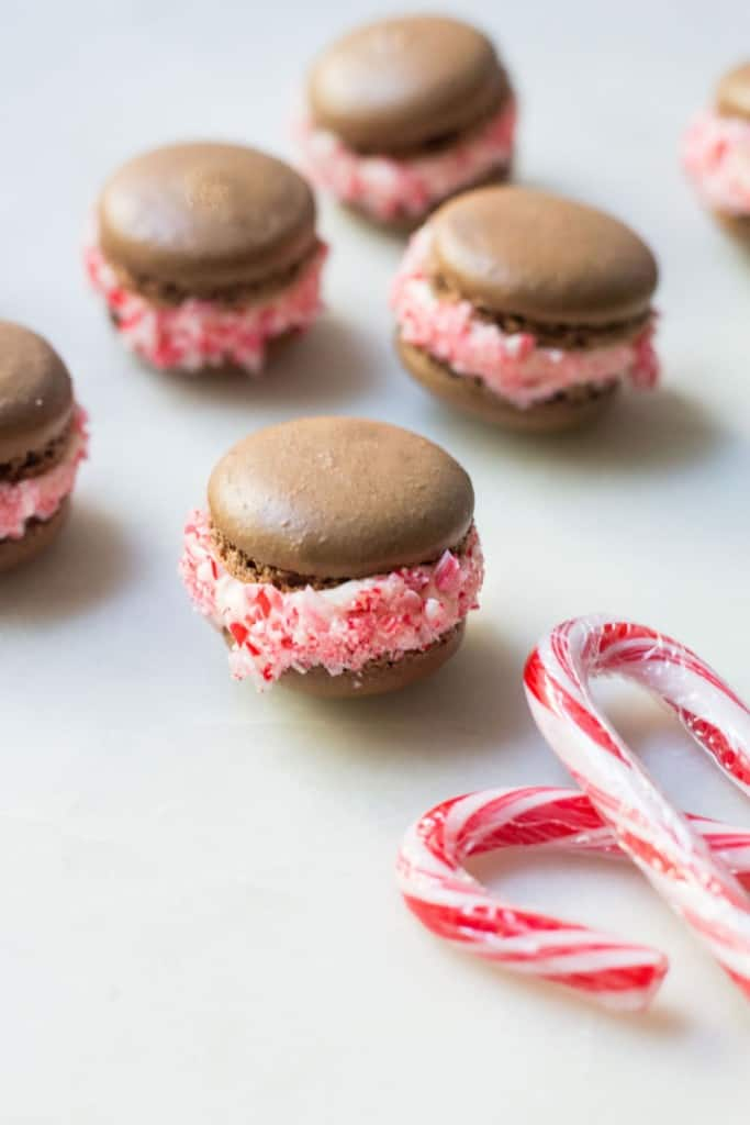 close-up shot of chocolate macarons with peppermint filling and candy canes